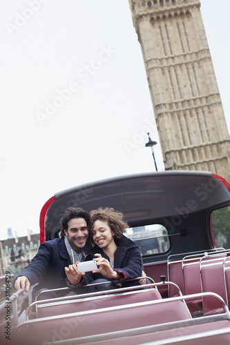 Happy couple taking self-portrait with camera phone on double decker bus