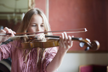 Serious girl playing violin