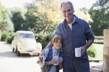 Portrait of smiling grandfather and grandson hugging with coffee mugs in driveway