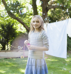 Portrait of smiling girl blowing bubbles in backyard