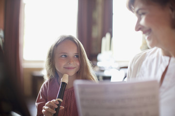 Grandmother with sheet music watching granddaughter practice on recorder