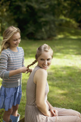 Girl braiding sister?s blonde hair in park