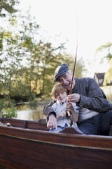 Grandfather and grandson fishing in boat