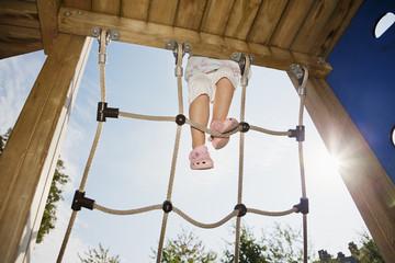 Girl climbing rope at sunny playground