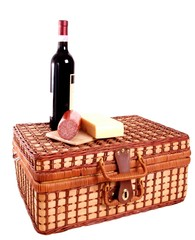 Picnic basket with wine, cheese and sausage on top