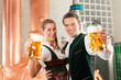 Paar in Tracht mit Bier Glas in Brauerei
