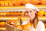Female baker selling bread by basket in bakery