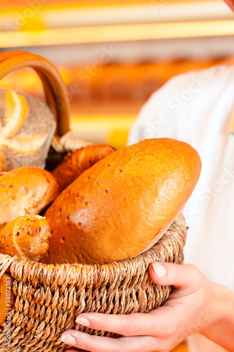 Female baker in bakery selling bread by basket