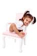 enfant charmeuse assise sur ancienne chaise rose et blanche