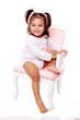 petite fille souriante sur une chaise ancienne couleur rose