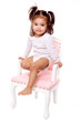 petite fille avec des couettes et body sur chaise rose