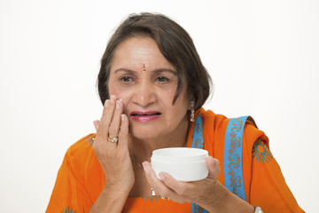 Mature woman skincare applying anti-wrinkle cream