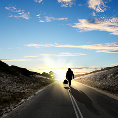 Man walking away at dawn along road