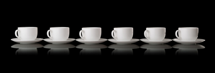 White cups and saucers on a black background