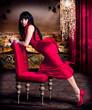 schöne Frau im roten Abendkleid mit erleuchteter Stadt im Hinte