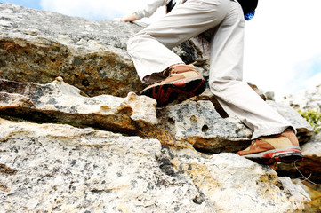 Feet with hiking boots climbing a rocky wall
