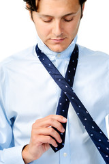 Man starts to tying his tie