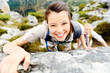 Hiker smiles while climbing up a rocky wall