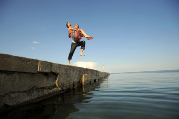 Young couple jumping from a pier inro the water