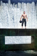 Fit  man with ball  on  footbridge at the waterfall