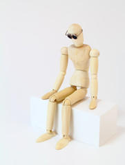 Wooden character sitting in deep thought