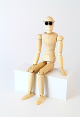 Wooden character sitting and looking at the camera.