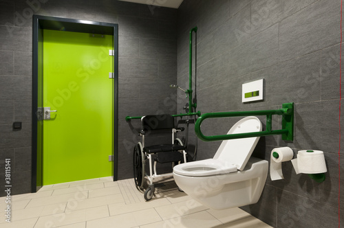 a toilet for disabled people with green bars, wheelchair