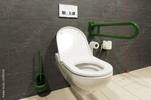 extreme wide angle of a white toilet for disabled persons