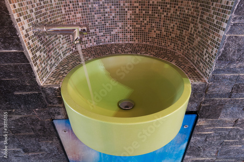 green washbowl with water tap niched with mosaic tiles