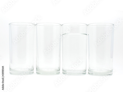 Four glasses with water in one glass on white background