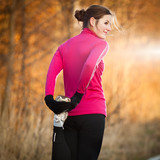 Fototapety Young woman stretching before her run outdoors on a cold fall