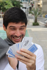 A businessman is holding cards, at the street