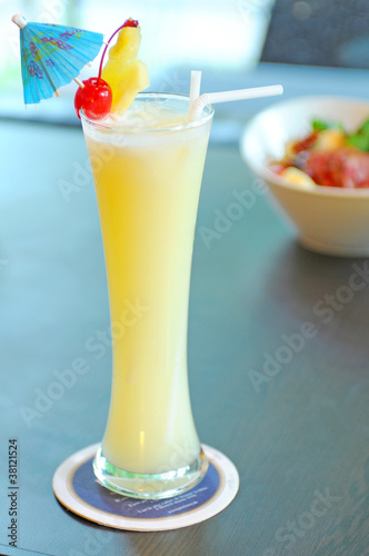 Yellow alcohol cocktail with pineapple, lemon