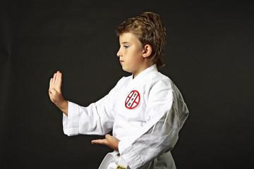 мальчик в кимоно занимается спортом