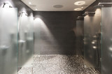 several showers seperated with walls of glass