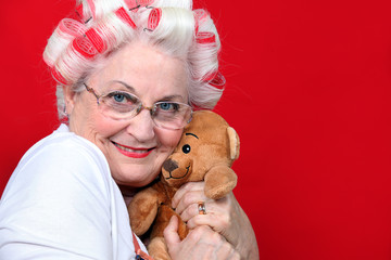 An old woman with hairroller on hugging a teddy bear.