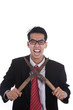 Stressed businessman with grass shears