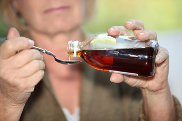 Woman taking cough medicine