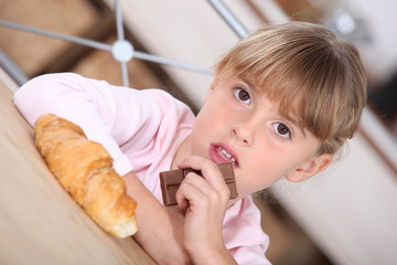 Young girl with a croissant and bar of chocolate