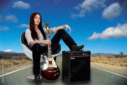 Stylized female guitarist with her amp on the road