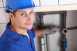 Young male plumber installing pipes