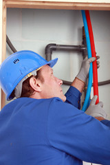 Plumber feeding hot and cold pipes behind a wall