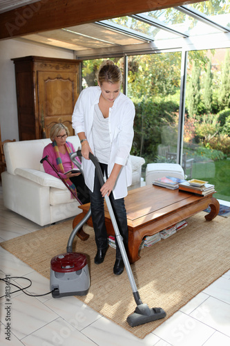 Young woman vacuuming