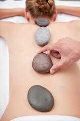 Beautiful woman receiving hot stone massage