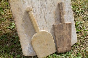 Deux battoirs en bois posés contre une planche à laver