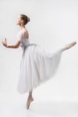 Beautiful ballerina dances in a white dress