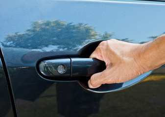 a hand pulling car door handle
