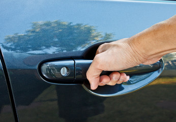 a hand pulling a car door handle