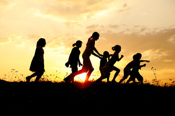 Silhouette, group of happy children  on meadow, summertime
