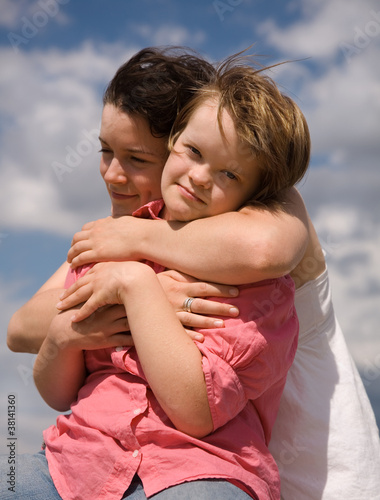 A girl embracing her sister with Down syndrome.